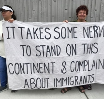 "Two people holding a sign that says, ""It takes some nerve to stand on this continent and complain about immigrants"""